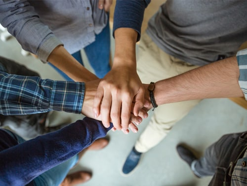 Image of a group of people with hands facing the centre of the circle in a team building exercise, showcasing the School Wellbeing Policy Checklist