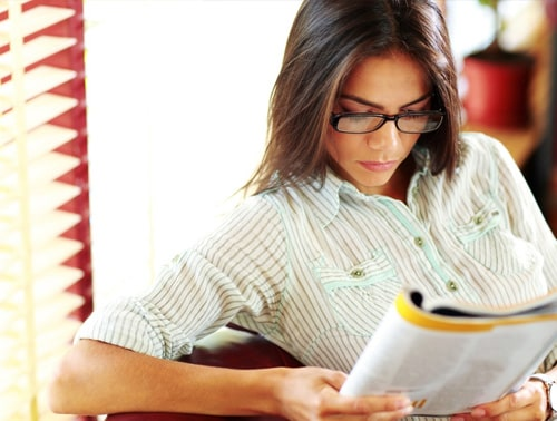 Image of a woman reading a magazine or research article showcasing The Importance of Homework blog.