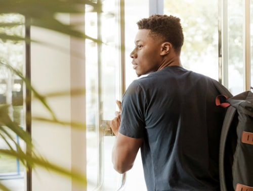 Image of a student walking through a corridor and leaving the building for the Supporting Student Wellbieng in Schools article.