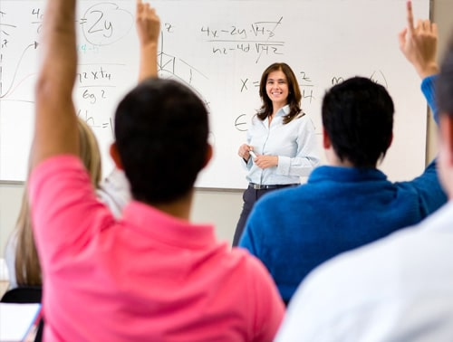 Image of students with their hands raised in a classroom and a teacher in front of a whiteboard for The Benefits of Seating Plans for Students resource